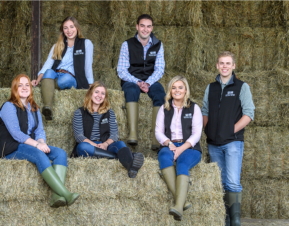 Young farmers sat on hay bails