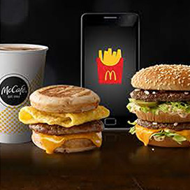 McCafé® drink in paper cup, Sausage, Egg & Cheese McGriddles®, smartphone and Big Mac®