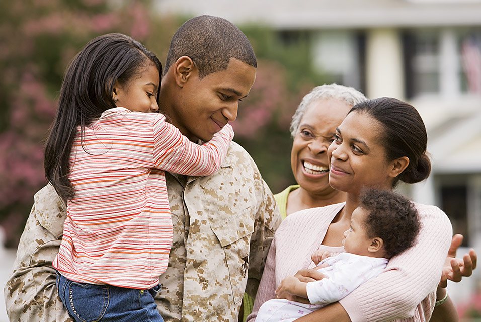 A man in military fatigues greeting his family
