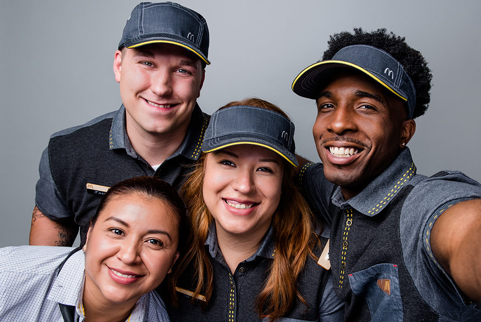 Two men and two women in McDonald's uniforms smiling and posing for a camera