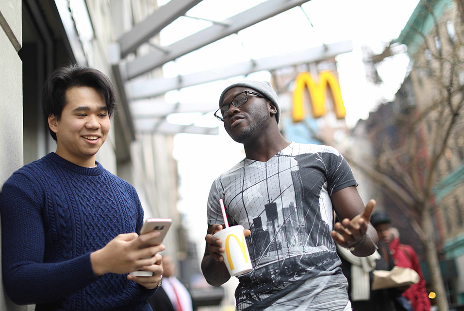 Two young men, one with a McDonald's cup, talking outside a McDonald's restaurant.