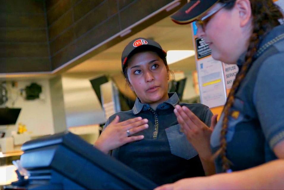 Woman in McDonald's uniform talking to another woman in a McDonald's crew uniform at a register