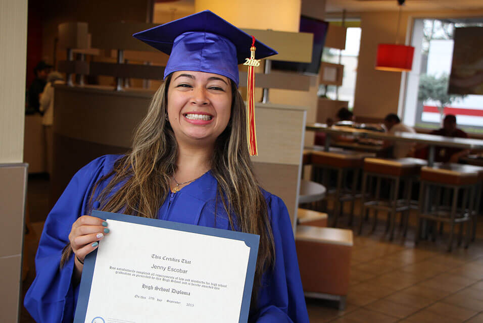 Young woman in a graduation robe smiling and displaying a diploma