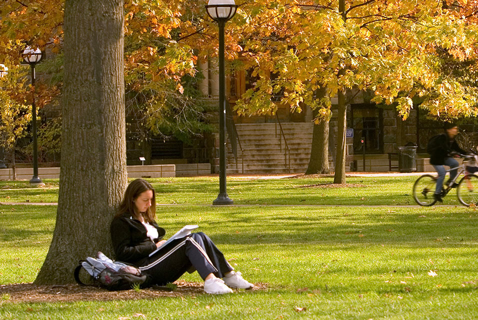 Young woman studying with a textbook and backback outside under a tree