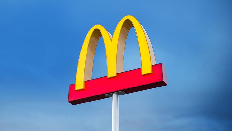 golden arches restaurant sign shown with a blue sky background