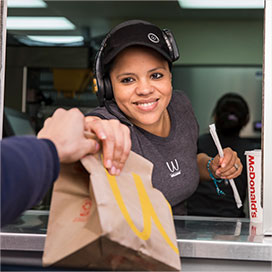 Woman handing over a McDonald's bag at the drive thru window