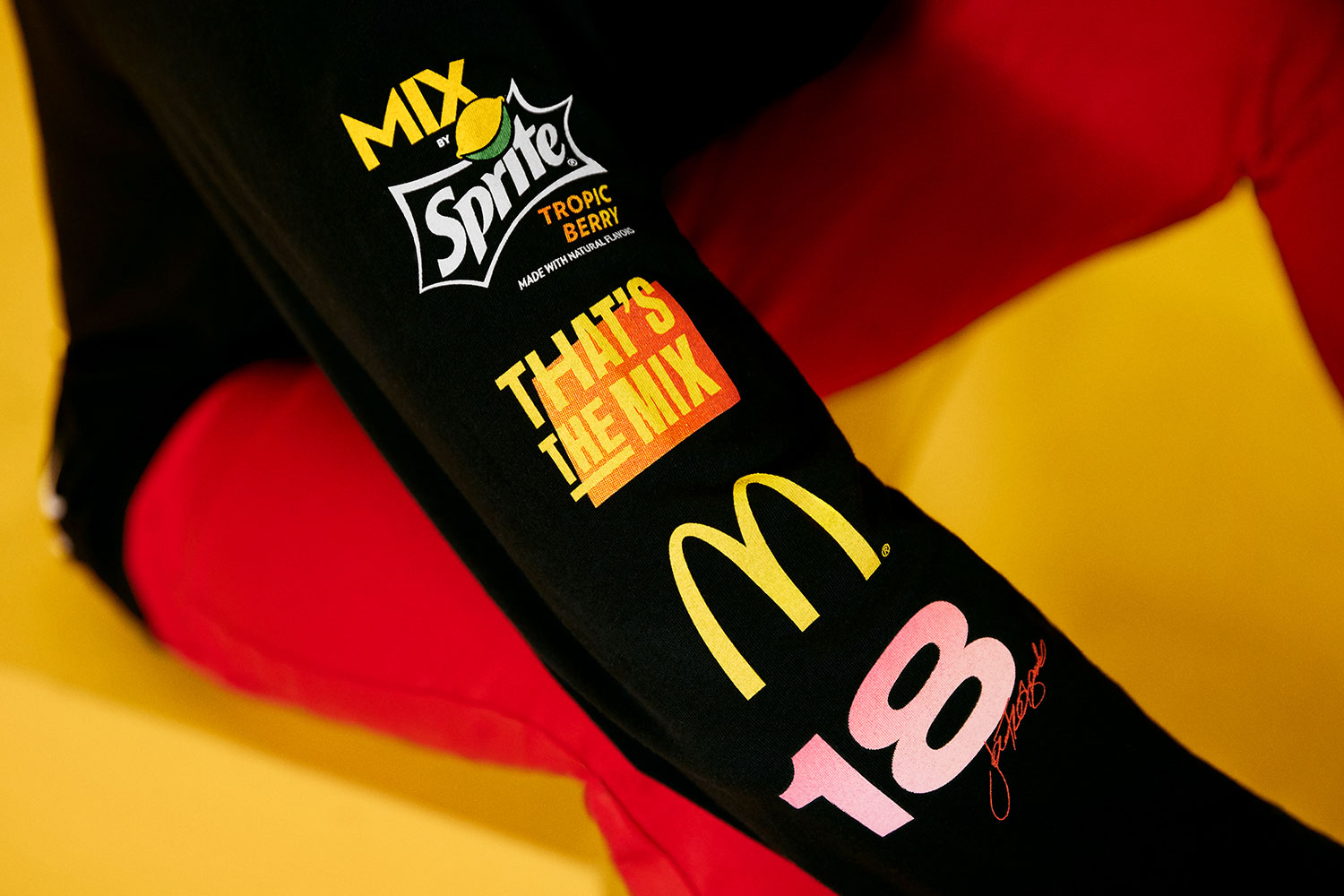 closeup of a black shirt sleeve, showing That's the MIX, MIX by Sprite™ Tropic Berry, McDonald's and Joe Freshgoods logos with number 18
