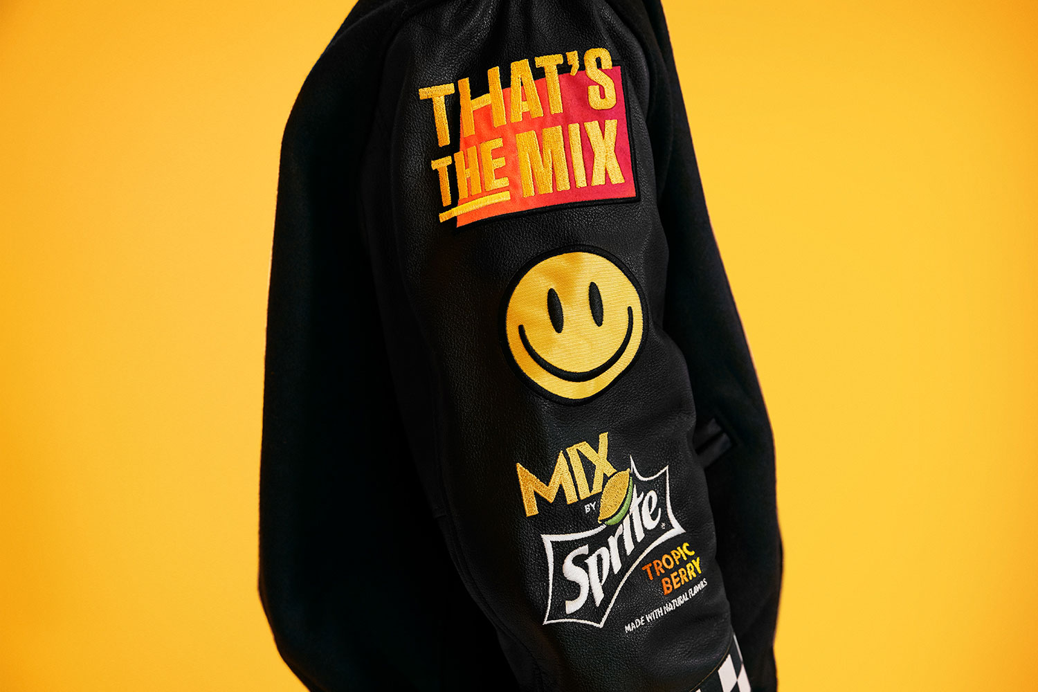 closeup of a black jacket sleeve, showing That's the MIX and MIX by Sprite™ Tropic Berry logos and a smiley face