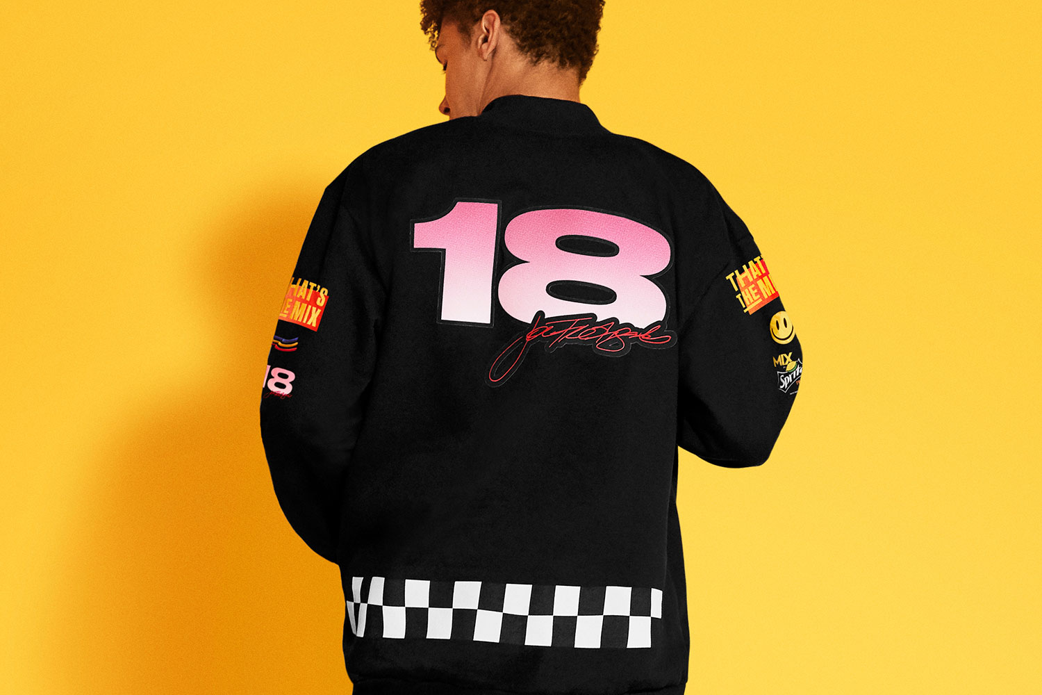 back of a black letterman jacket with Joe Freshgoods logos with number 18 and a black and white checker pattern
