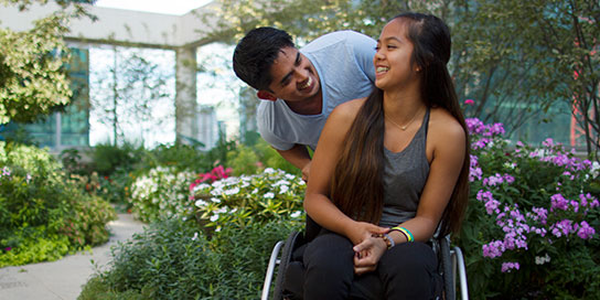 Young woman in a wheelchair smiling at a male family member in a flower garden.