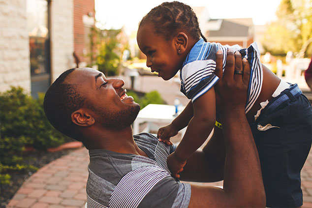 Smiling father lifting young daughter in the air