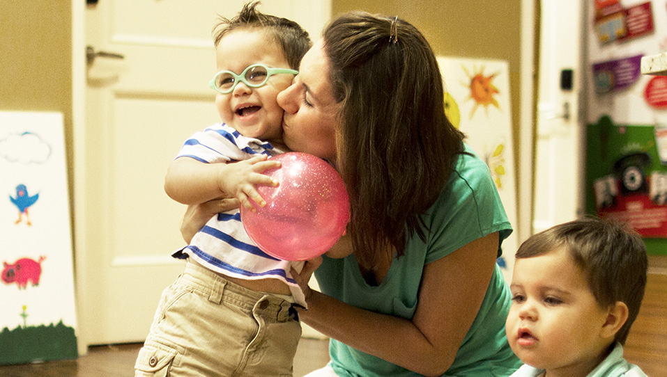 Mom holding toddler son and kissing his cheek, RMHC