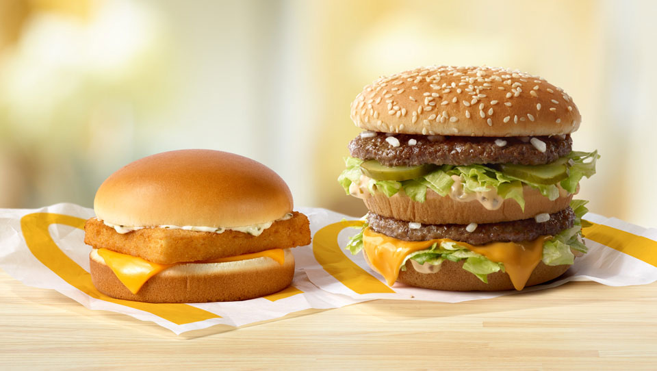 Filet-o-Fish and a Big Mac Sandwiche on a table.