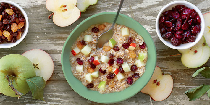 Bowl of Fruit & Maple Oatmeal on a table with halved apples