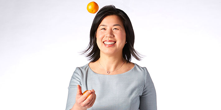 Woman in a grey shirt tossing an apple into the air