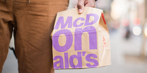Close up of a person holding a McDonald's bag.