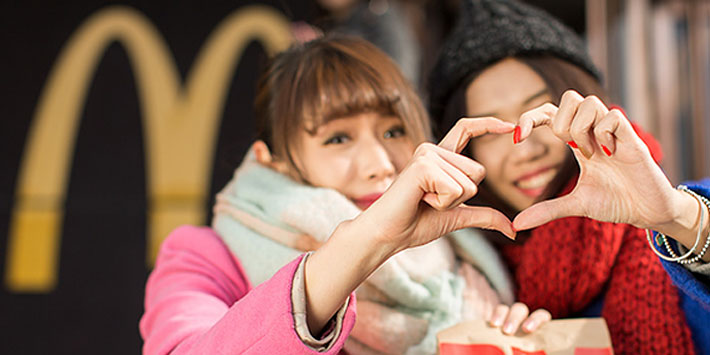Two women making a heart-shaped sign with their hands in front of a Golden Arches sign