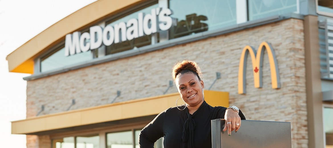 Une franchisée de McDonald's qui sourit devant son restaurant