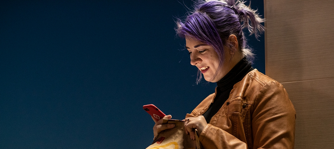Woman smiling at phone holding a McDonald's bag