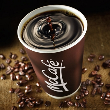 A McCafé Coffee cup surrounded by coffee beans