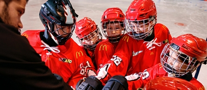 atoMc Hockey team huddling with coach before a game