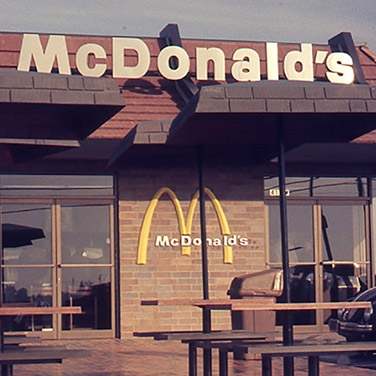 A modern exterior of a McDonald's storefront with arches symbol