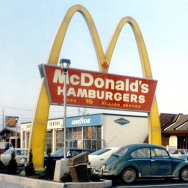 A retro McDonald's signage with arches in front of a McDonald's restaurant