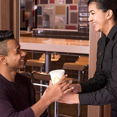a mcdonald's staff serving a cup to a seated customer