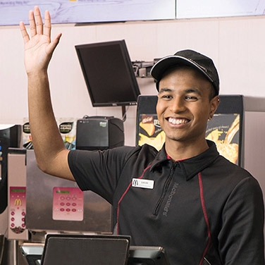 mcdonald's staff smiling with hand raised to take a customer's order