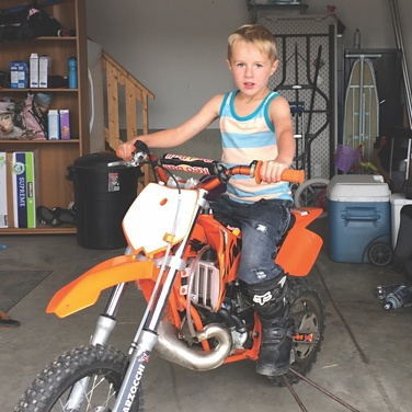 Boy siting on an orange dirt bike