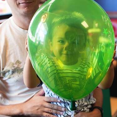 Baby smiling through balloon
