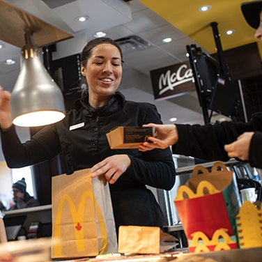 McDonald's staff member cheerily packing an order into a brown food bag