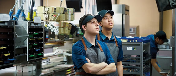 Two McDonald's staff member reading an incoming order on a tv monitor