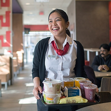 McDonald's Staff member cheerily serving a tray food