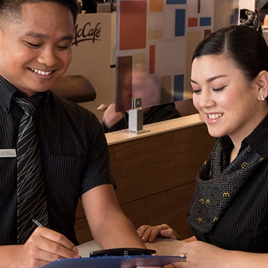 McDonald's staff members smiling while reviewing a document