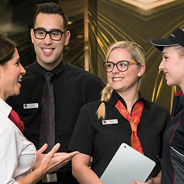 four mcdonald's staff members smiling and chatting
