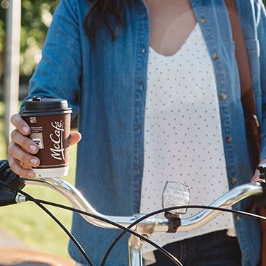 a woman standing over her bike holding a mccafé coffee cup