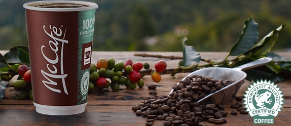 McCafé to go cup sitting on wood table with Columbia as the backdrop. On the table, there is a scoop with coffee beans and coffee plant twig with berries. Rainforest Alliance Certified Logo is located in the bottom right corner.
