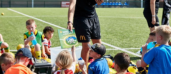 Group of young kids sitting around a football coach handing out fun football activity book