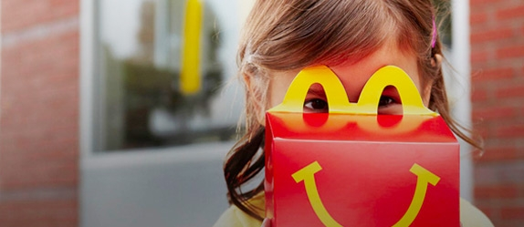 Young girl holding red Happy Meal box close to her face and looking through the yellow handle