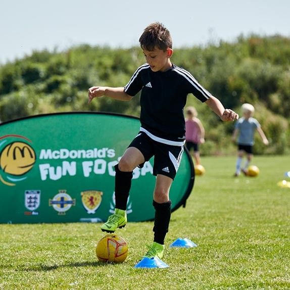 Young boy practicing football skills at a McDonald's fun football session