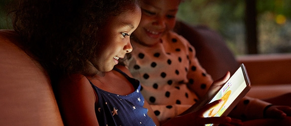 Two young girls playing game on tablet device together