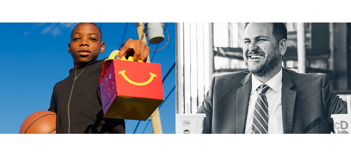 young boy holds a mcdonalds happy meal box in one hand and a basketball in the other and a laughing man in a suit enjoys a mcdonald's burger and drink at a table with a friend