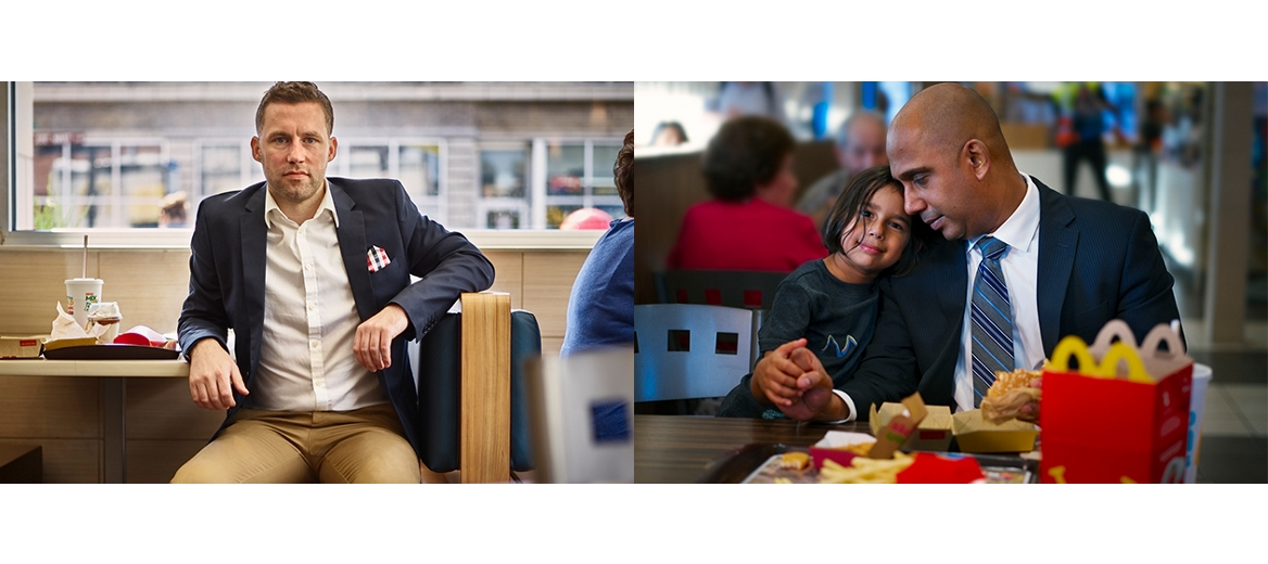 man in a blue blazer sitting in a mcdonald's booth and a young girl putting her head on the shoulder of a man in a suit at a mcdonald's table